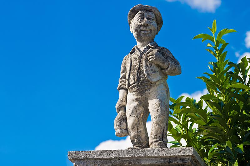 Statua di un contadino con il fiasco di vino in mano