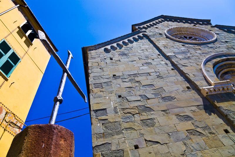 Una croce in ferro battuto e la chiesa di San Pietro