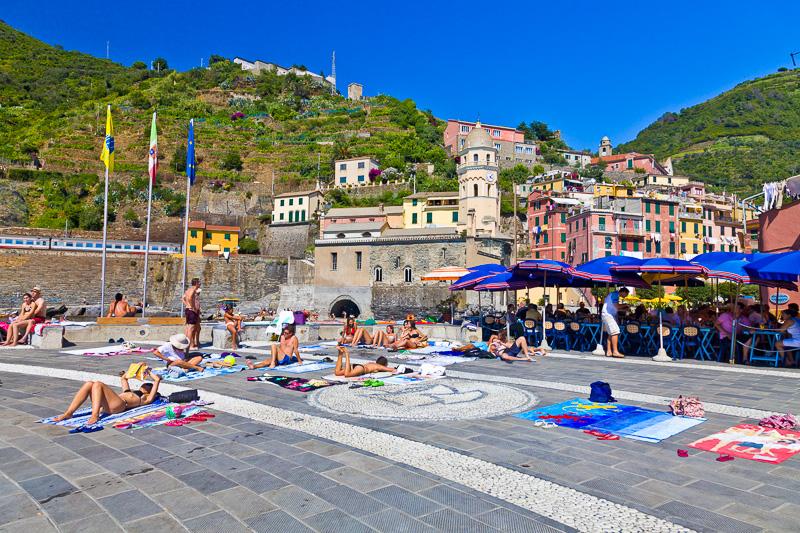 Piazzetta del molo piena di turisti a prendere il sole